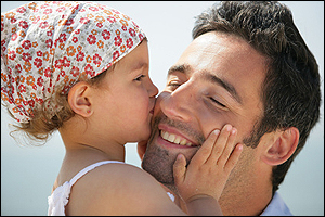 Little girl kissing father on cheek